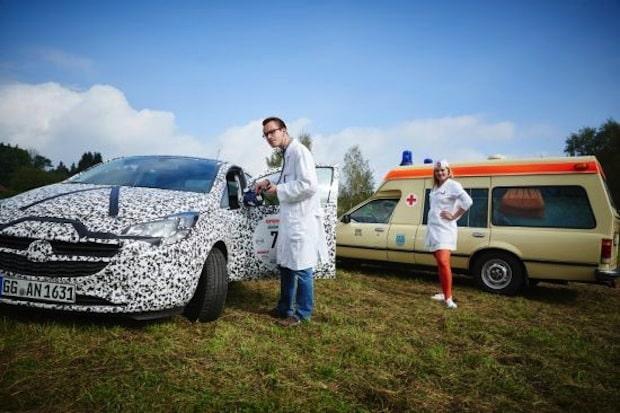 """Bild: """"Ärzte"""" auf Rädern bei der Creme21: Neuer Corsa in schwarzweißer Erlkönigtarnung wird vom Team des Opel Commodore Krankenwagen """"untersucht""""."""